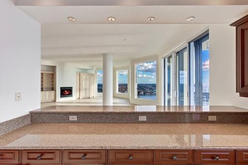 Küche mit Blick auf Wohn-Essbereich mit Kamin und Meerblick